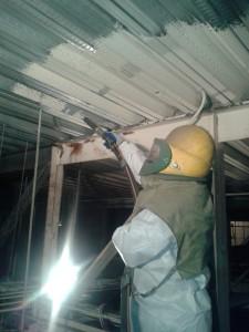 Individual in HAZMAT suit sandblasting metal ceiling
